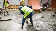 man shoveling concrete to be formed into concrete floor